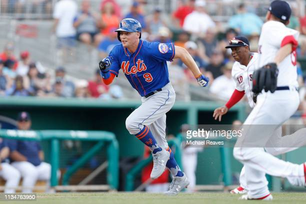 Brandon Nimmo of the New York Mets runs home to score a run in the fifth inning on a wild pitch against the Boston Red Sox during the Grapefruit...