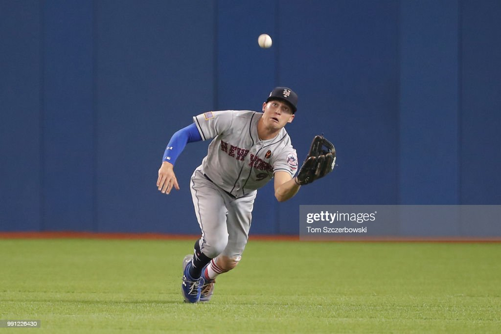 Brandon Nimmo #9 of the New York Mets tracks down a fly ball in the eighth inning during MLB game action against the Toronto Blue Jays at Rogers Centre on July 3, 2018 in Toronto, Canada.