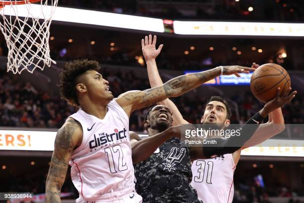Brandon Paul of the San Antonio Spurs has a shot blocked by Kelly Oubre Jr #12 of the Washington Wizards during the second half at Capital One Arena...