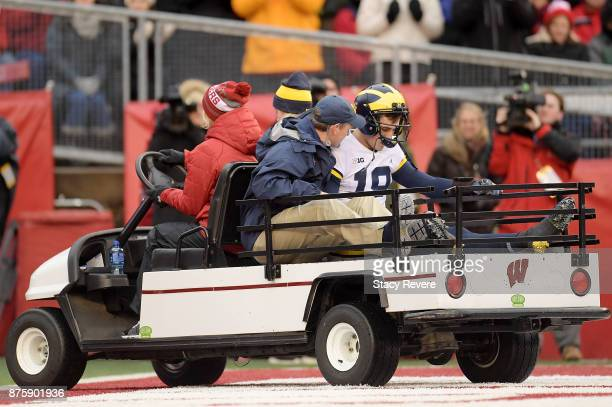 Brandon Peters of the Michigan Wolverines is carted off the field following an injury during the third quarter of a game against the Wisconsin...