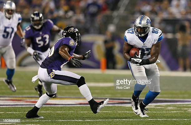 Brandon Pettigrew of the Detroit Lions catches a pass in front of Emanuel Cook of the Baltimore Ravens during the first half at MT Bank Stadium on...