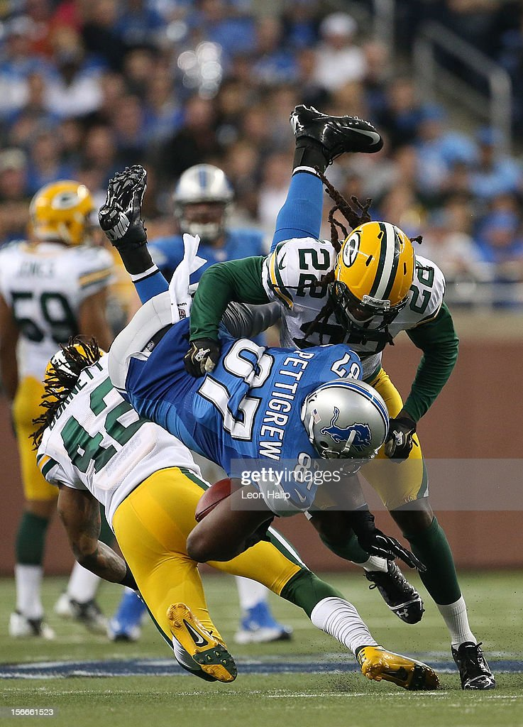 Brandon Pettigrew #87 of the Detroit Lions makes a catch during the game and is stopped by Morgan Burnett #42 and Jerron McMillian #22 of the Green Bay Packers at Ford Field on November 18, 2012 in Detroit, Michigan. The Packers defeated the Lions 24-20.