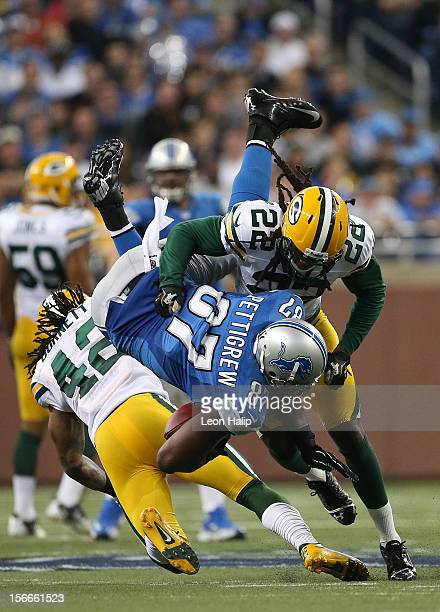 Brandon Pettigrew of the Detroit Lions makes a catch during the game and is stopped by Morgan Burnett and Jerron McMillian of the Green Bay Packers...