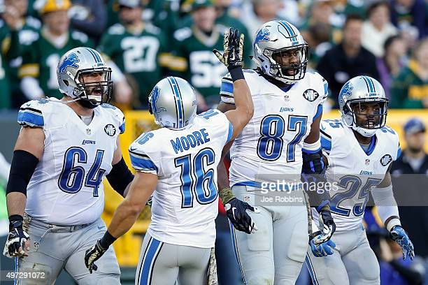 Brandon Pettigrew of the Detroit Lions reacts with teammates Travis Swanson, Lance Moore and Theo Riddick after scoring a touchdown in the third...