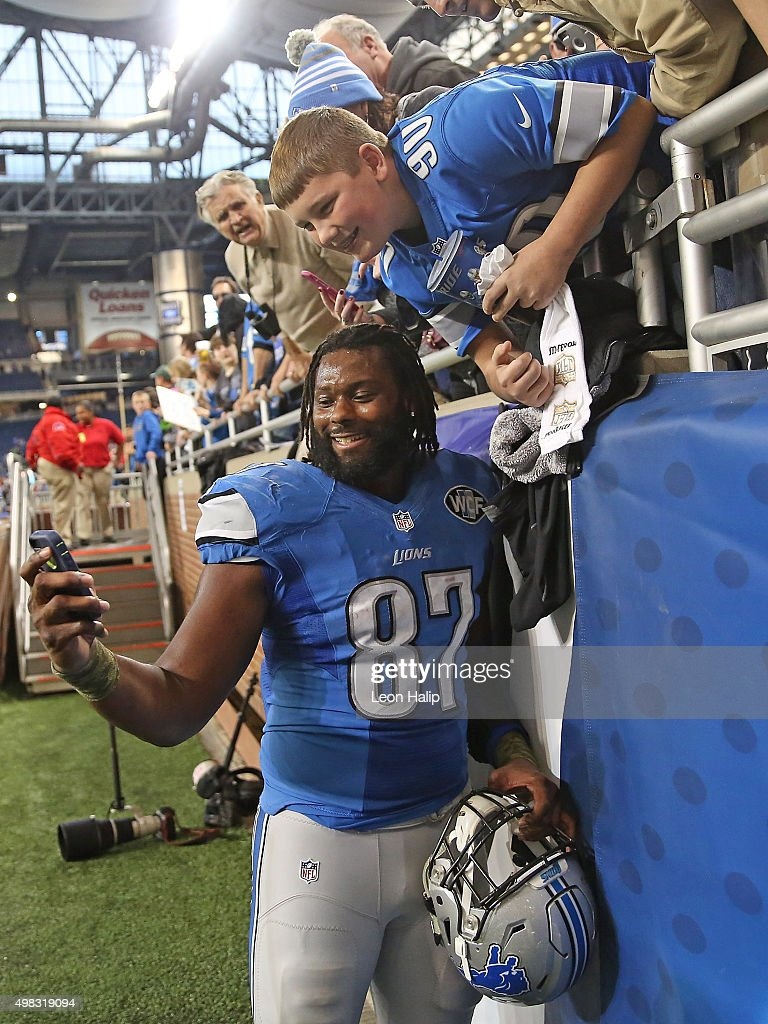 Brandon Pettigrew #87 of the Detroit Lions takes a selfie with a fan after the game against the Oakland Raiders on November 22, 2015 at Ford Field in Detroit, Michigan. The Lions defeated the Raiders 18-13.