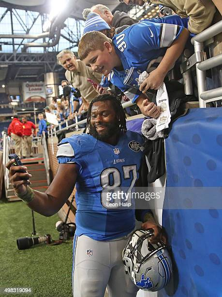 Brandon Pettigrew of the Detroit Lions takes a selfie with a fan after the game against the Oakland Raiders on November 22 2015 at Ford Field in...