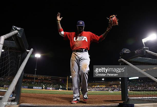 Brandon Phillips of Team USA holds up his arms as he walks into the dugout during the spring training game against the Colorado Rockies at Salt River...