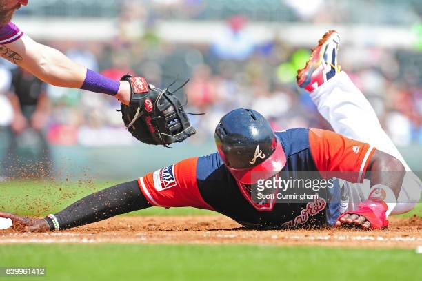 Brandon Phillips of the Atlanta Braves dives back safely to first base in the fourth inning against the Colorado Rockies at SunTrust Park on August...