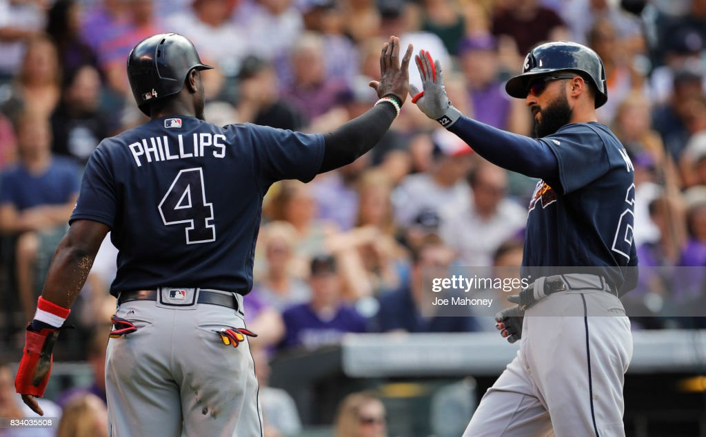 Brandon Phillips (4) of the Atlanta Braves greets Nick Markakis (22) of the Atlanta Braves after the pair scored on double by Matt Adams (18) of the Atlanta Braves against the Colorado Rockies in the seventh inning at Coors Field on August 17, 2017 in Denver, Colorado.