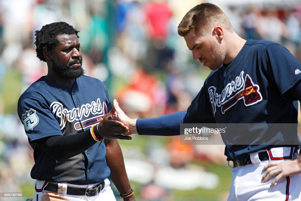 Brandon Phillips #4 of the Atlanta Braves is congratulated by Freddie Freeman #5 after an RBI-single in the fifth inning of a Grapefruit League spring training game against the Miami Marlins at Champion Stadium on March 20, 2017 in Lake Buena Vista, Florida. The Marlins defeated the Braves 9-3.