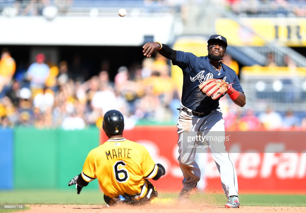 Brandon Phillips #4 of the Atlanta Braves turns a double play in front of Starling Marte #6 of the Pittsburgh Pirates during the eighth inning at PNC Park on April 9, 2017 in Pittsburgh, Pennsylvania.