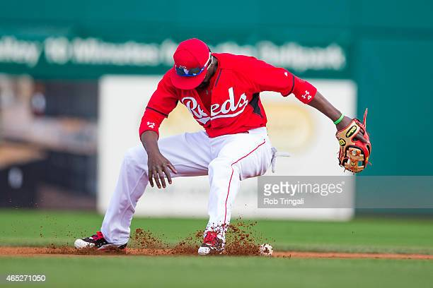 Brandon Phillips of the Cincinnati Reds bobbles a ball before throwing a runner out in the fourth inning during a spring training game against the...