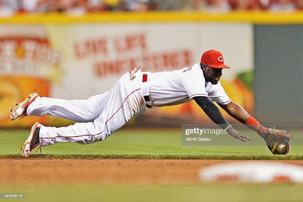 Brandon Phillips #4 of the Cincinnati Reds dives to make a stop on a ground ball hit by Anthony Rizzo #44 of the Chicago Cubs in the eighth inning at Great American Ball Park on July 9, 2014 in Cincinnati, Ohio. Phillips injured his left thumb on the play and left the game as Cincinnati defeated Chicago 4-1.