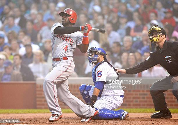 Brandon Phillips of the Cincinnati Reds follows through on a grand slam scoring teammates Zack Cozart Joey Votto and Homer Bailey as catcher Dioner...