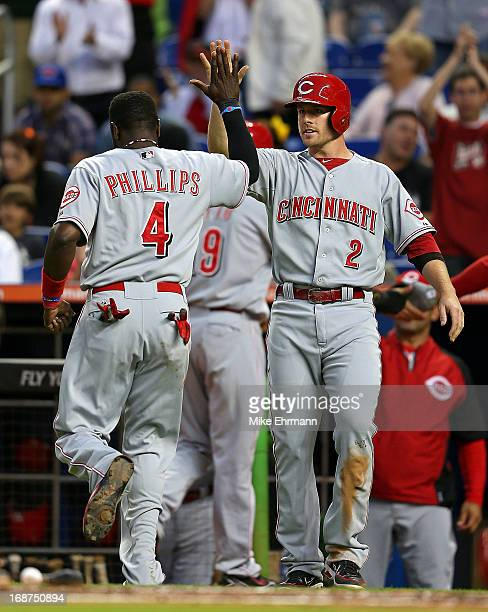 Brandon Phillips of the Cincinnati Reds is congratulated by Zack Cozart after scoring during a game against the Miami Marlins at Marlins Park on May...