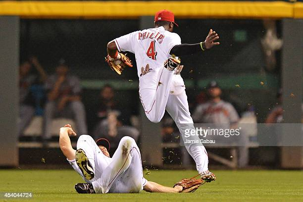 Brandon Phillips of the Cincinnati Reds leaps over right fielder Chris Heisey of the Cincinnati Reds after making an over the shoulder catch of a hit...
