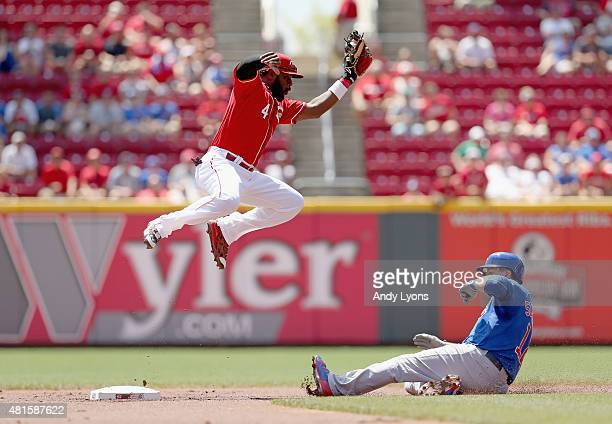 Brandon Phillips of the Cincinnati Reds leaps to catch the ball while Kyle Schwarber of the Chicago Cubs slides safely in for a stolen base during...