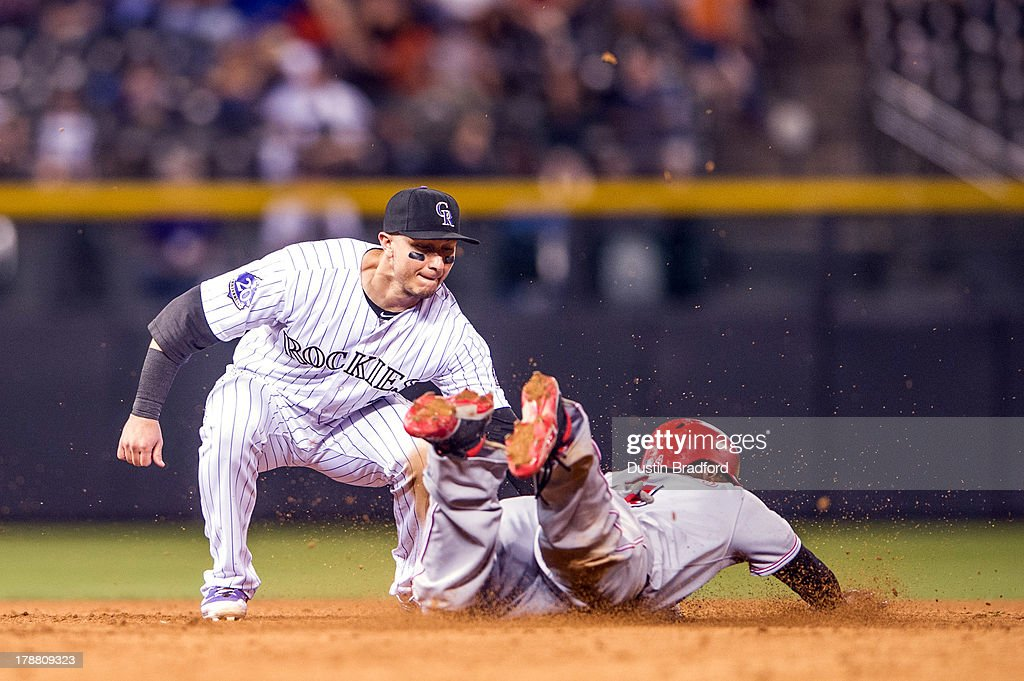 Brandon Phillips #4 of the Cincinnati Reds slides in safely to second base on a wild pitch under a tag attempt by Troy Tulowitzki #2 of the Colorado Rockies during the ninth inning of a game at Coors Field on August 30, 2013 in Denver, Colorado. The Rockies beat the Reds 9-6.