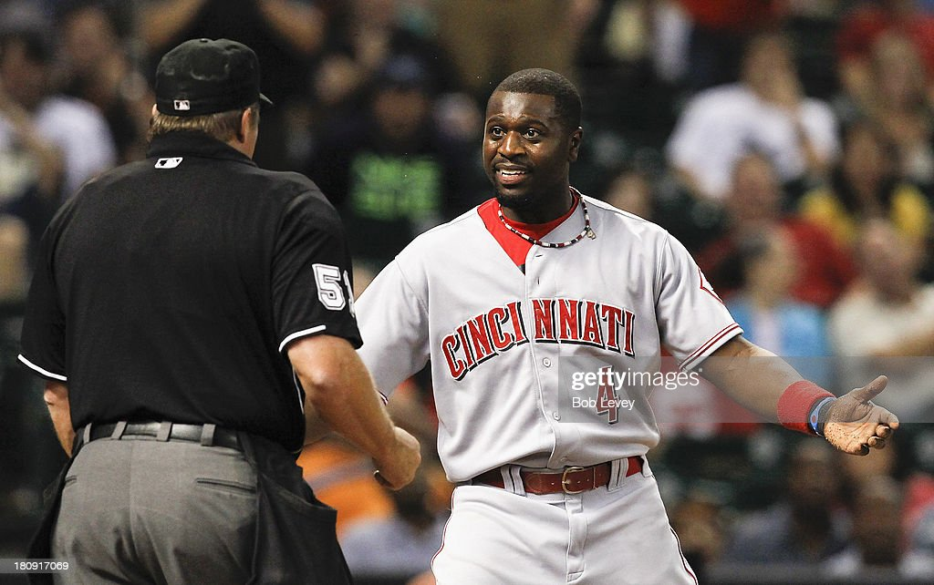 Brandon Phillips #4 of the Cincinnati Reds talks with home plate umpire Marvin Hudson after he was called out trying to score from third base in the sixth inning against the Houston Astros at Minute Maid Park on September 17, 2013 in Houston, Texas.