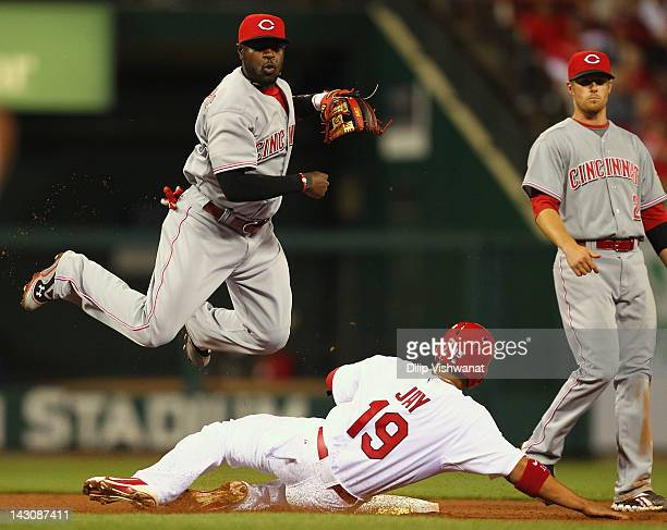 Brandon Phillips of the Cincinnati Reds turns a double play over Jon Jay of the St. Louis Cardinals at Busch Stadium on April 18, 2012 in St. Louis,...