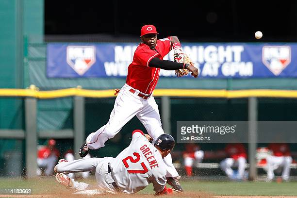 Brandon Phillips of the Cincinnati Reds turns a double play over Tyler Greene of the St Louis Cardinals at Great American Ball Park on May 14 2011 in...