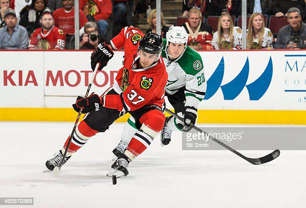 Brandon Pirri of the Chicago Blackhawks approaches the puck as Cody Eakin of the Dallas Stars watches from behind during the NHL game on December 03,...