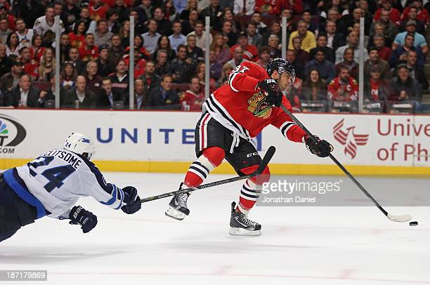 Brandon Pirri of the Chicago Blackhawks shoots and scores a goal under pressure from Grant Clitsome of the Winnipeg Jets at the United Center on...