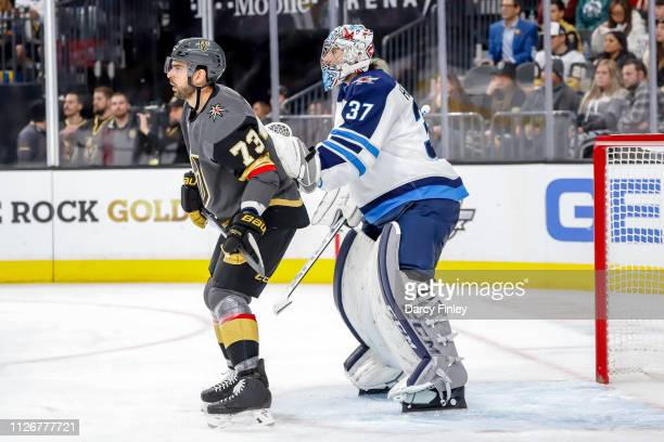 Brandon Pirri of the Vegas Golden Knights and goaltender Connor Hellebuyck of the Winnipeg Jets keep an eye on the play during second period action...