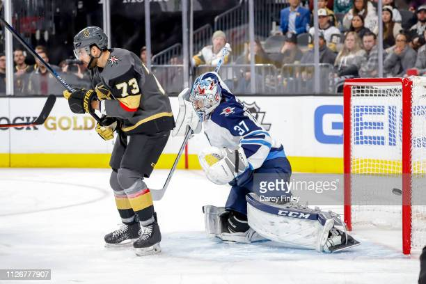 Brandon Pirri of the Vegas Golden Knights sets a screen in front of goaltender Connor Hellebuyck of the Winnipeg Jets as the puck goes in the net for...