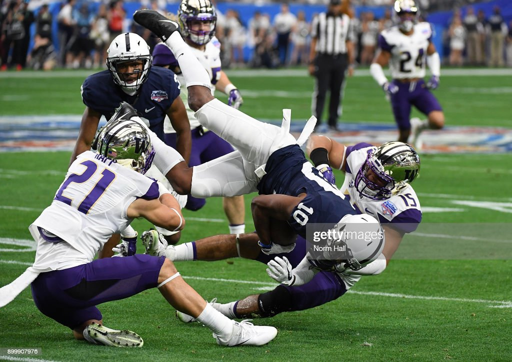 Brandon Polk #10 of the Penn State Nittany Lions is tackled by Alex Cook #5 and Taylor Rapp #21 of the Washington Huskies during the first half of the Playstation Fiesta Bowl at University of Phoenix Stadium on December 30, 2017 in Glendale, Arizona.