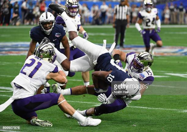 Brandon Polk of the Penn State Nittany Lions is tackled by Alex Cook and Taylor Rapp of the Washington Huskies during the first half of the...