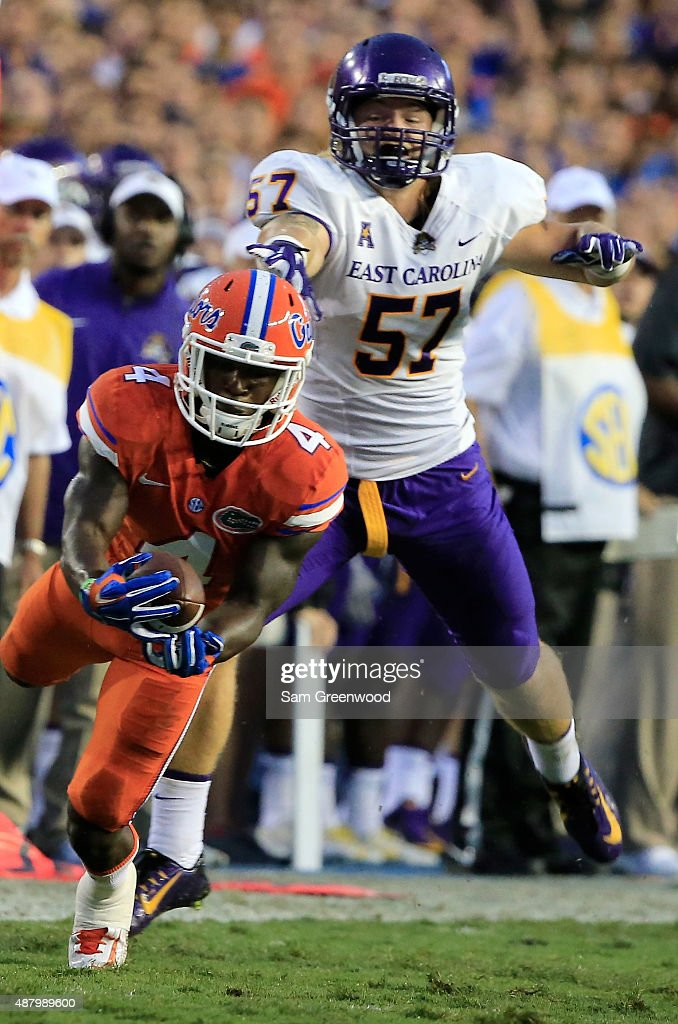 Brandon Powell #4 of the Florida Gators makes a reception against Joe Allely #57 of the East Carolina Pirates during the game at Ben Hill Griffin Stadium on September 12, 2015 in Gainesville, Florida.
