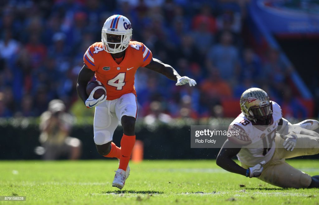Brandon Powell #4 of the Florida Gators runs past Ro'Derrick Hoskins #18 of the Florida State Seminoles during the first half of the game at Ben Hill Griffin Stadium on November 25, 2017 in Gainesville, Florida.