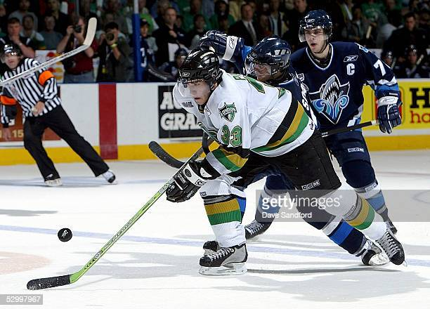 Brandon Prust of the London Knights breaks away from Mario Jr Scalzo and MarcAntoine Pouliot of the Rimouski Oceanic during the Memorial Cup...