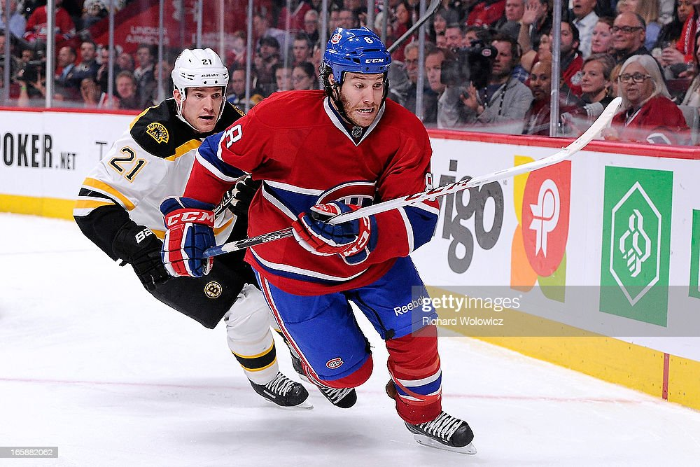 Brandon Prust #8 of the Montreal Canadiens and Andrew Ference #21 of the Boston Bruins chase the puck into the corner during the NHL game at the Bell Centre on April 6, 2013 in Montreal, Quebec, Canada. The Canadiens defeated the Bruins 2-1.