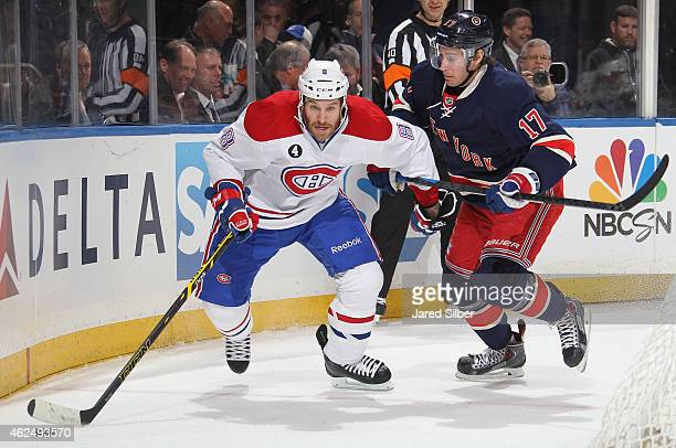 Brandon Prust of the Montreal Canadiens skates with the puck against John Moore of the New York Rangers at Madison Square Garden on January 29 2015...