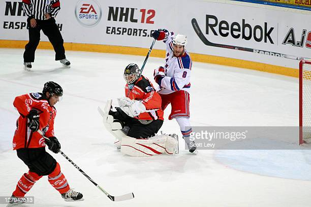 Brandon Prust of the New York Rangers gets tangled up with Jussi Markkanen of EV Zug at the Bossard Arena during the 2011 NHL Compuware Premiere...