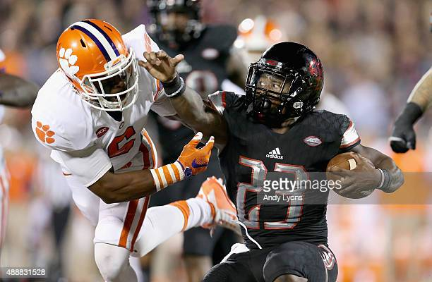 Brandon Radcliff of the Louisville Cardinals runs with the ball while defended by Dorian O'Daniel of the Clemson Tigers at Papa John's Cardinal...