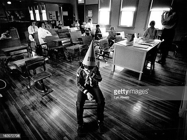 OCT 16 1987 Brandon Richier holds back a giggle when he is asked to demonstrate the dunce cap and corner chair for his cub scout troop visiting the...