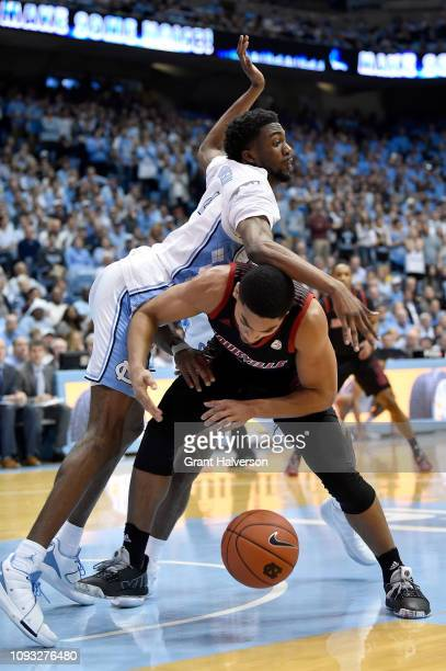 Brandon Robinson of the North Carolina Tar Heels battles Christen Cunningham of the Louisville Cardinals for a loose ball during the first half of...