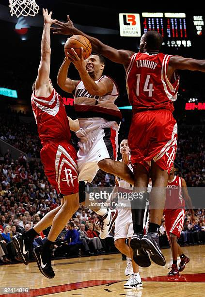 Brandon Roy of the Portland Trail Blazers drives against Carl Landry and David Andersen of the Houston Rockets during the season opener on October 27...