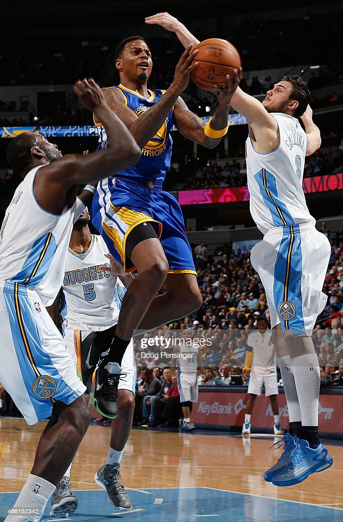Brandon Rush #4 of the Golden State Warriors lays up a shot against J.J. Hickson #7 and Danilo Gallinari #8 of the Denver Nuggets at Pepsi Center on March 13, 2015 in Denver, Colorado.