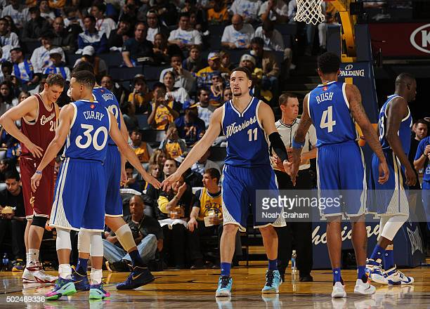 Brandon Rush Stephen Curry and Klay Thompson of the Golden State Warriors shake hands after a play against the Cleveland Cavaliers on December 25...