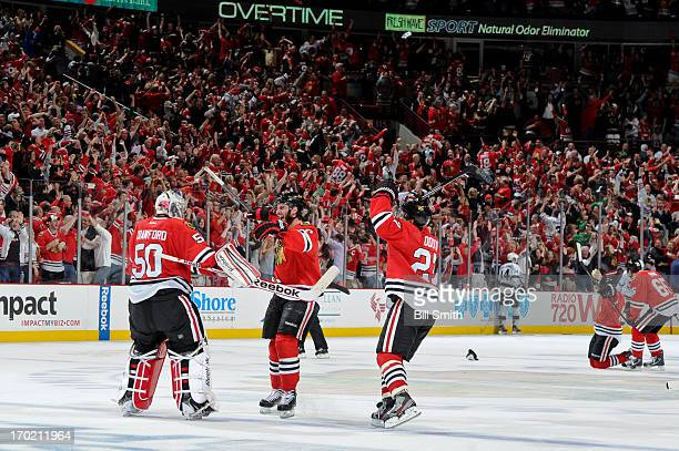 Brandon Saad and Johnny Oduya of the Chicago Blackhawks skate over to teammate goalie Corey Crawford to celebrate after defeating the Los Angeles...