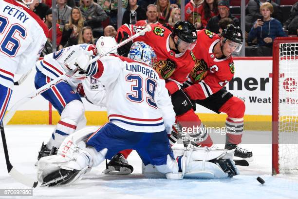 Brandon Saad and Jonathan Toews of the Chicago Blackhawks watch the puck next to goalie Charlie Lindgren of the Montreal Canadiens in the third...