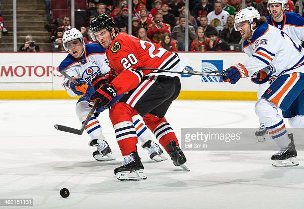 Brandon Saad of the Chicago Blackhawks and David Perron of the Edmonton Oilers chase after the puck as Ryan Jones of the Oilers reaches from behind...