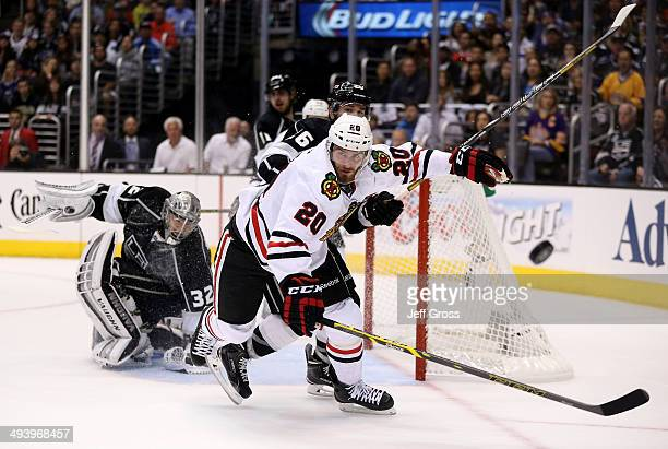 Brandon Saad of the Chicago Blackhawks and Slava Voynov of the Los Angeles Kings go after the puck in the first period in Game Four of the Western...