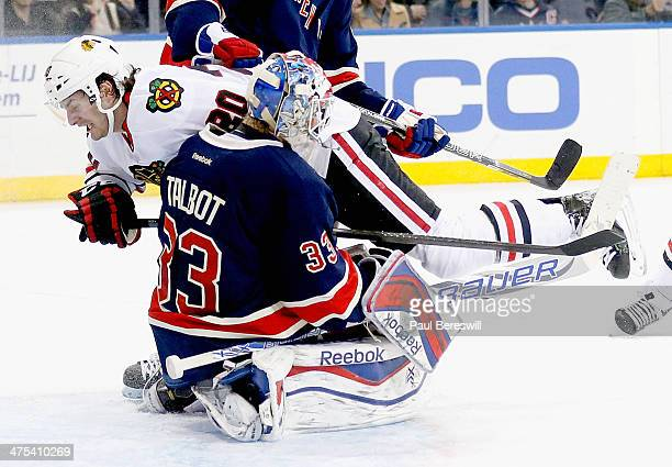Brandon Saad of the Chicago Blackhawks bowls over goalie Cam Talbot of the New York Rangers as Talbot made the save in the third period of an NHL...