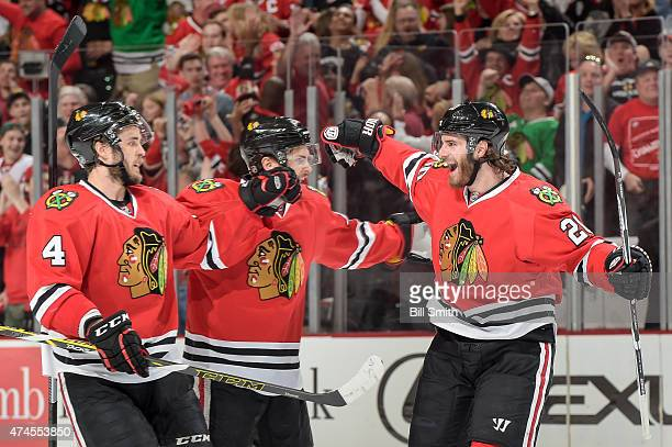 Brandon Saad of the Chicago Blackhawks celebrates with Marcus Kruger and Niklas Hjalmarsson after scoring against the Anaheim Ducks in the first...