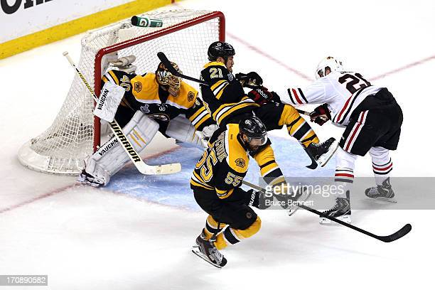 Brandon Saad of the Chicago Blackhawks collides with Andrew Ference of the Boston Bruins in front of Tuukka Rask in Game Four of the 2013 NHL Stanley...